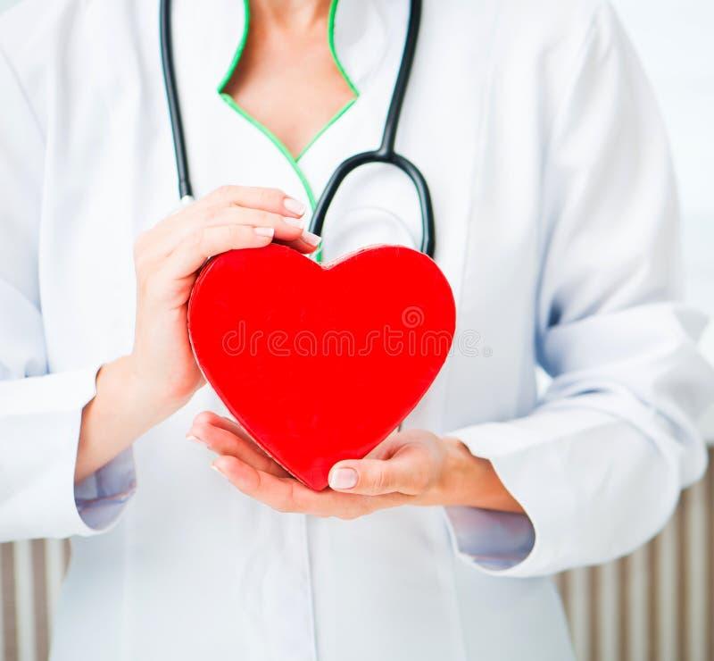 Doktors händer med röd hjärta arkivfoton