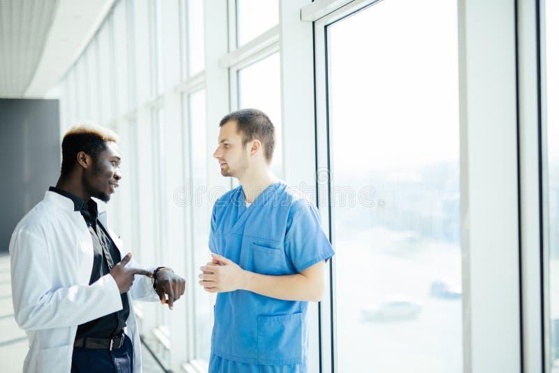 Doktors- möte Diskuterar det säkra doktorsanseendet för blandat lopp två i sjukhus och patienten royaltyfri bild