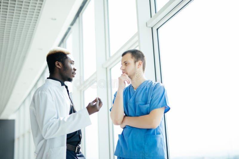 Doktors- möte Diskuterar det säkra doktorsanseendet för blandat lopp två i sjukhus och patienten royaltyfri fotografi