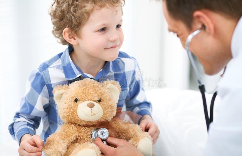 Doktors- och barnpatient Läkaren undersöker pysen vid stetoskopet Medicin- och för terapi för barn` s begrepp arkivbild