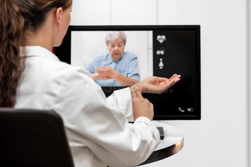 Doktors- och pensionärkvinna som tar pulsen, telemedicinen och videoen royaltyfri fotografi