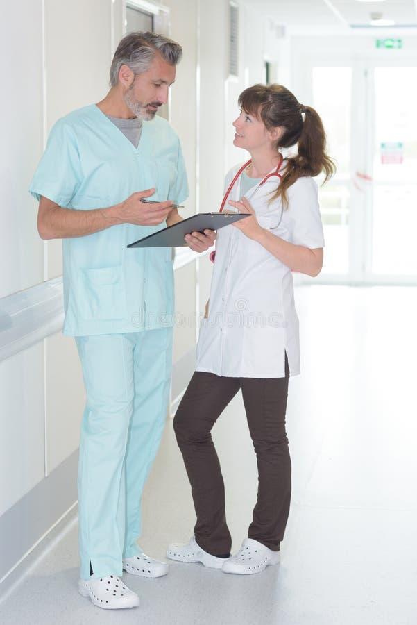 Doktors- och sjuksköterskaanseende i sjukhuskorridor arkivfoto