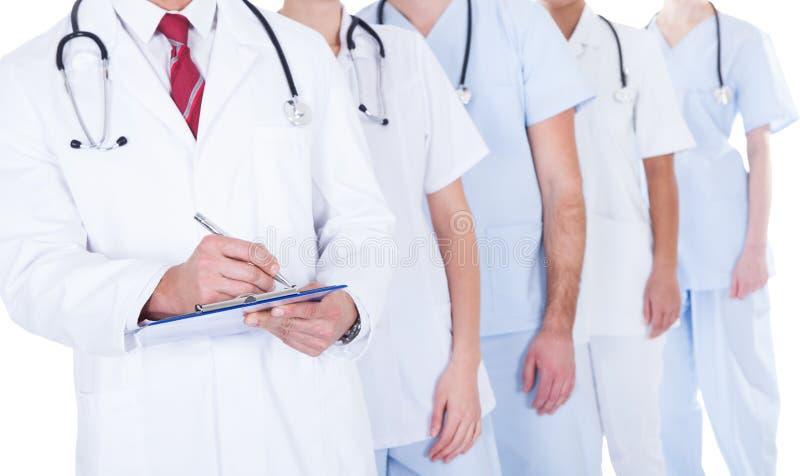 Doktorsanseende i grupphandstilrecept arkivbild