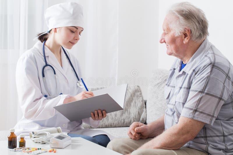 Doktorsbesök till den äldre patienten arkivbild