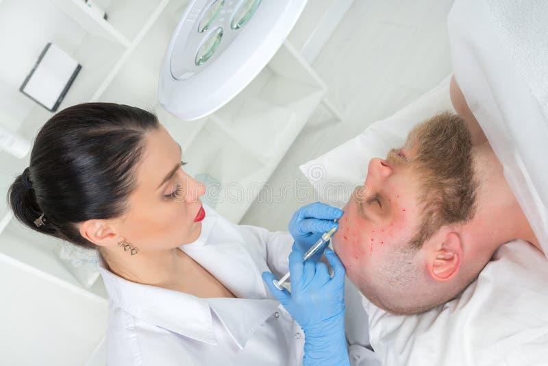 Doktorscosmetologisten gör den föryngra ansikts- injektionen fotografering för bildbyråer