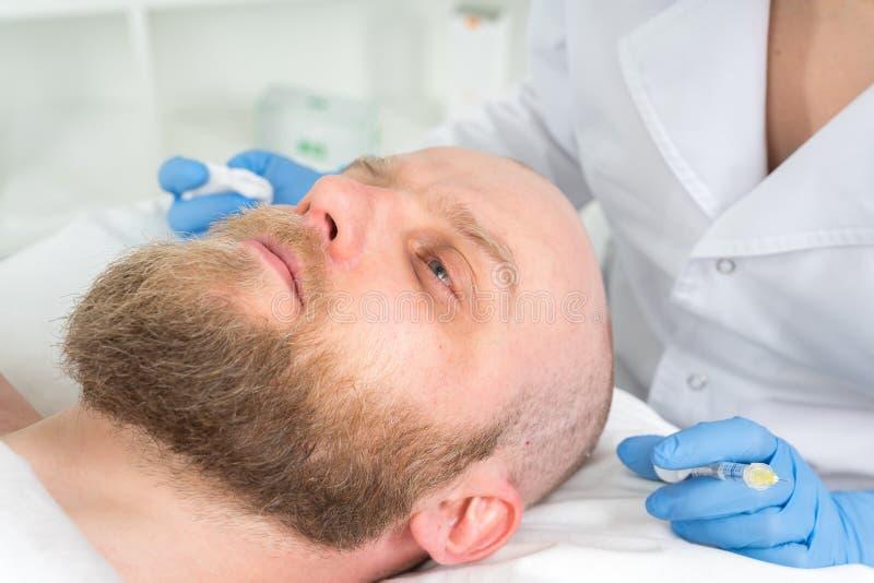 Doktorscosmetologisten gör det föryngra ansikts- injektiontillvägagångssättet för att dra åt, och släta rynkar på framsidahuden arkivfoto
