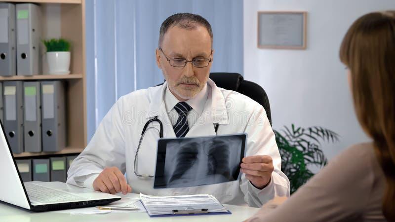 Doktorscy obserwuje płuca promieniowania rentgenowskie, cierpliwy czekanie dla diagnozy, gruźlicy ryzyko zdjęcia stock