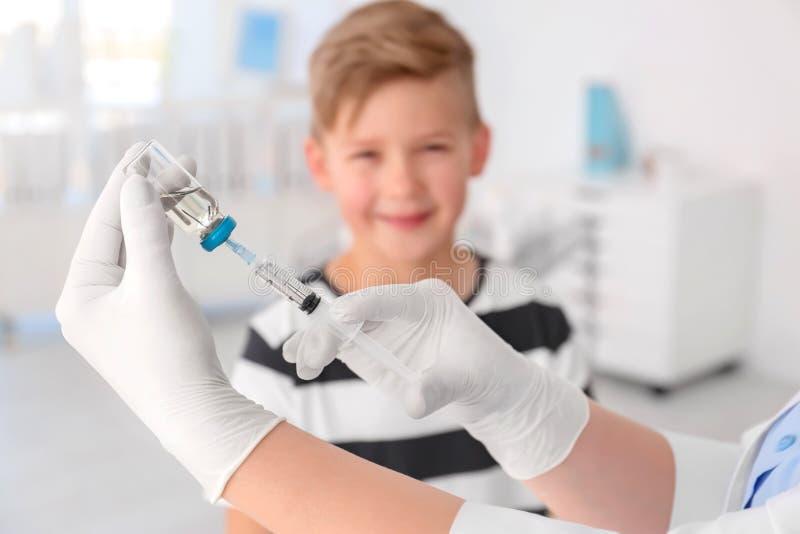 Doktorsfyllninginjektionsspruta med medicin och barnet arkivfoton