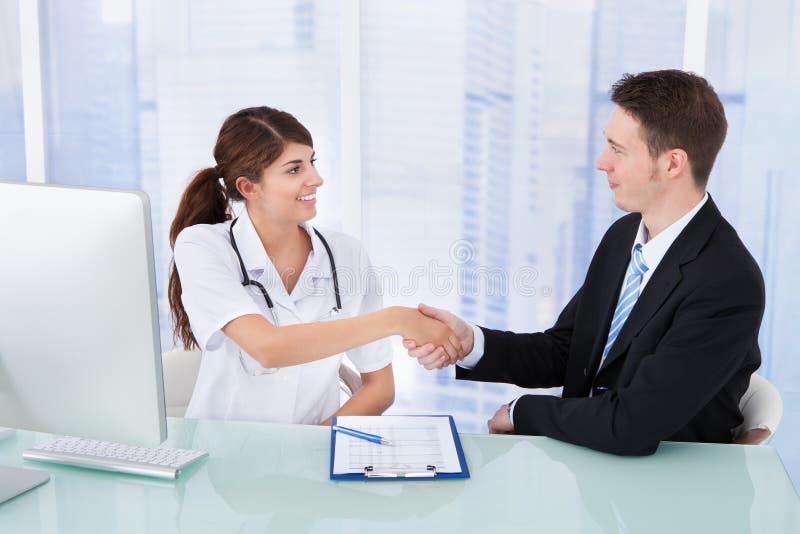 Doktorshälsningaffärsman i klinik royaltyfri foto