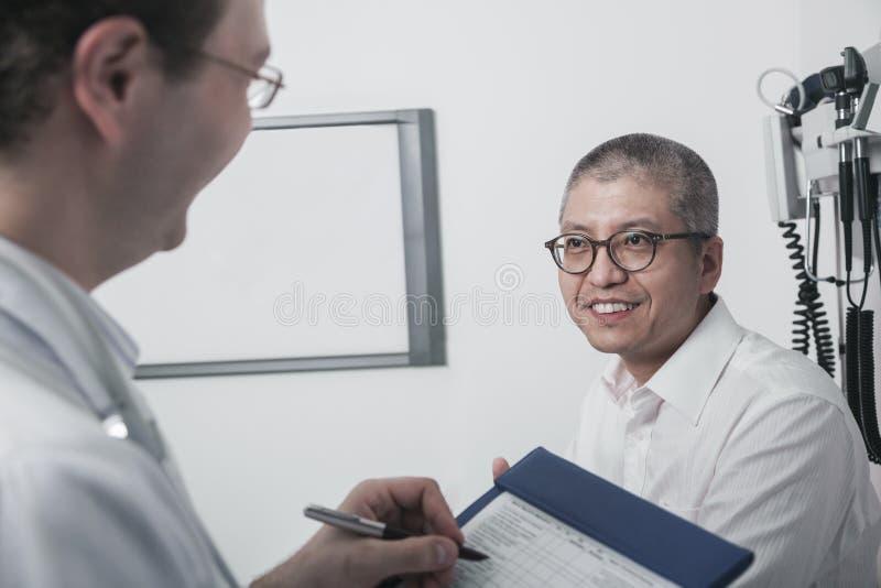 Doktorshandstil på medicinskt diagram med en le patient royaltyfri bild