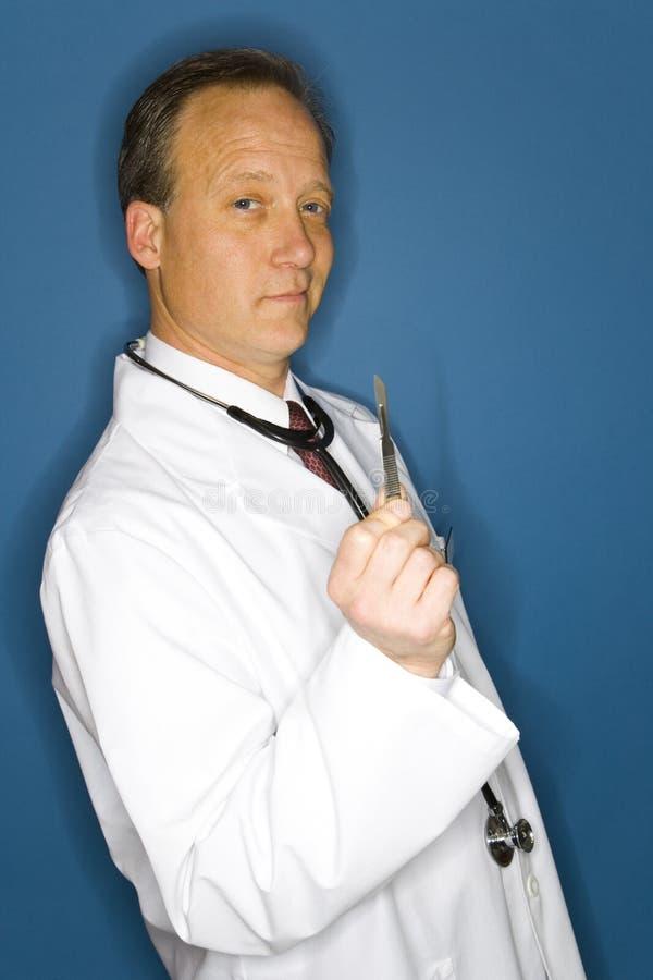 doktorsholdingskalpell royaltyfri foto