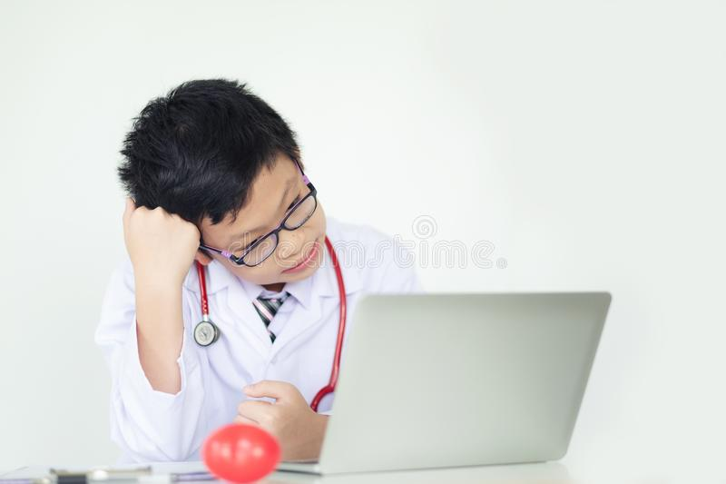 Doktorska chłopiec patrzejąca laptop z poważnym wyrażeniem na whi obrazy royalty free