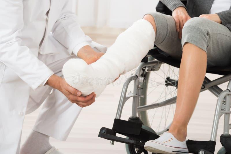 Doktorska Egzamininuje noga pacjent fotografia royalty free