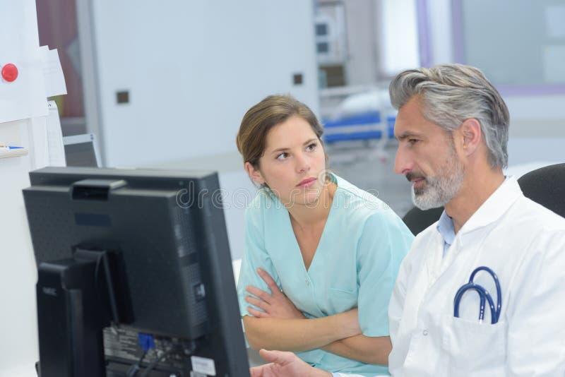 Doktorska i młoda żeńska pielęgniarka sprawdza pacjentów dokumenty obrazy stock