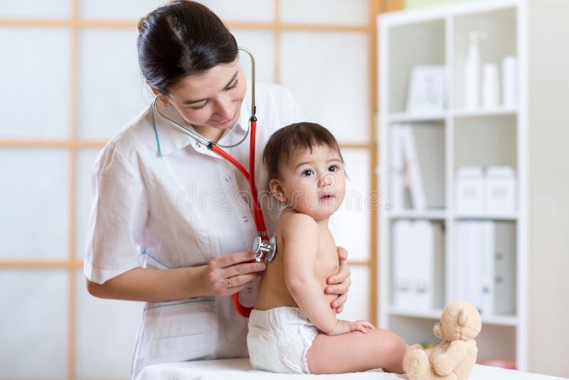 Doktorska kobieta egzamininuje płuca dzieciak z stetoskopem fotografia royalty free
