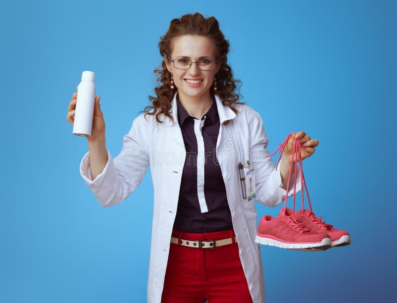 Doktorska kobieta pokazuje sprawno?ci fizycznych sneakers i obuwian? deodorizer ki?? zdjęcia stock