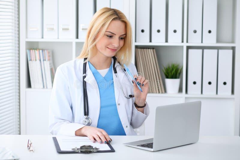 Doktorska kobieta przy pracą Portret rozochocony uśmiechnięty blondynka lekarz używa pastylka komputer przy biurkiem podczas gdy  fotografia royalty free