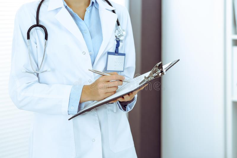 Doktorska kobieta wype?nia w g?r? medycznej formy w kliniki biurze Niewiadomy ?e?ski lekarz przy prac? podczas gdy stoj?cy prosto zdjęcie stock