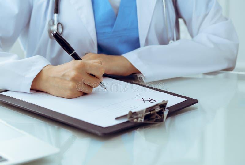 Doktorska kobieta wype?nia w g?r? recepty, zako?czenie r?ki Lekarz przy prac? Medycyny i opieki zdrowotnej poj?cie zdjęcia stock