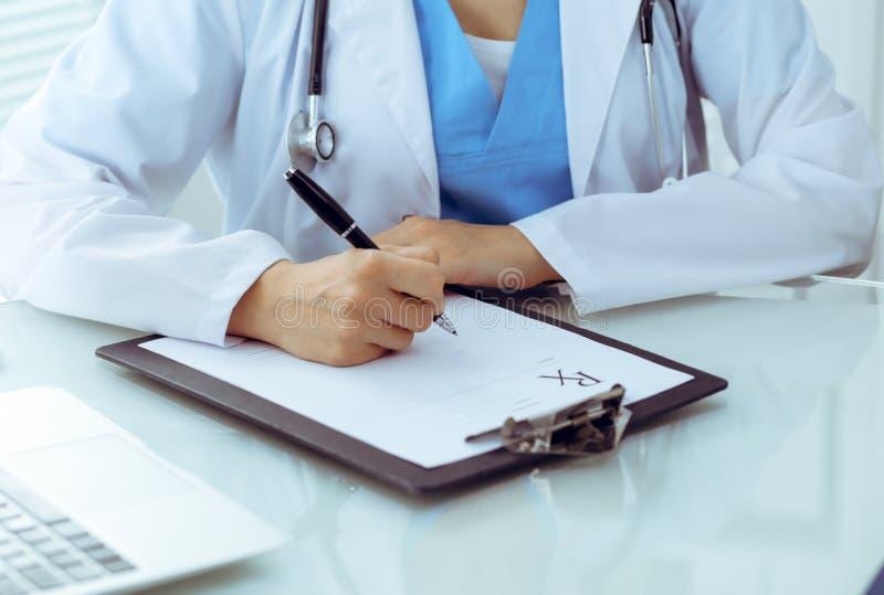 Doktorska kobieta wype?nia w g?r? recepty, zako?czenie r?ki Lekarz przy prac? Medycyny i opieki zdrowotnej poj?cie zdjęcia royalty free