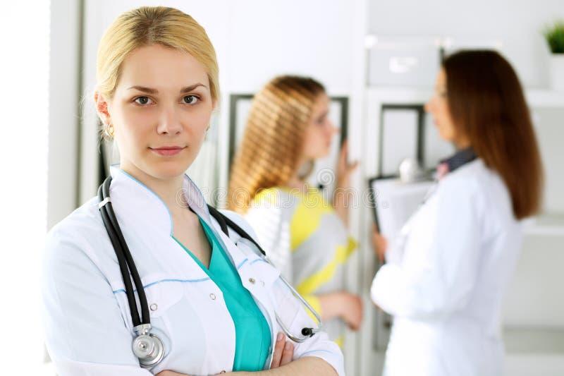 Doktorska kobiety lub pielęgniarki pozycja w szpitalnym biurze z jej kolegą w tle opieki oka opieki zdrowotnej higieny medycyna obrazy stock