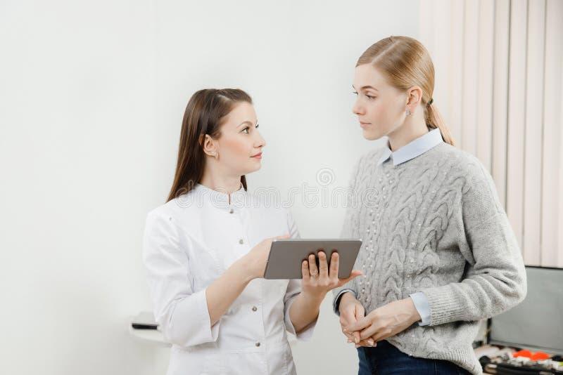 Doktorska oftalmolog dziewczyna z ciemnym bieżącym włosy pokazuje w pastylce i spojrzeniu przy cierpliwym blondynka ogonem, duzi  obraz stock