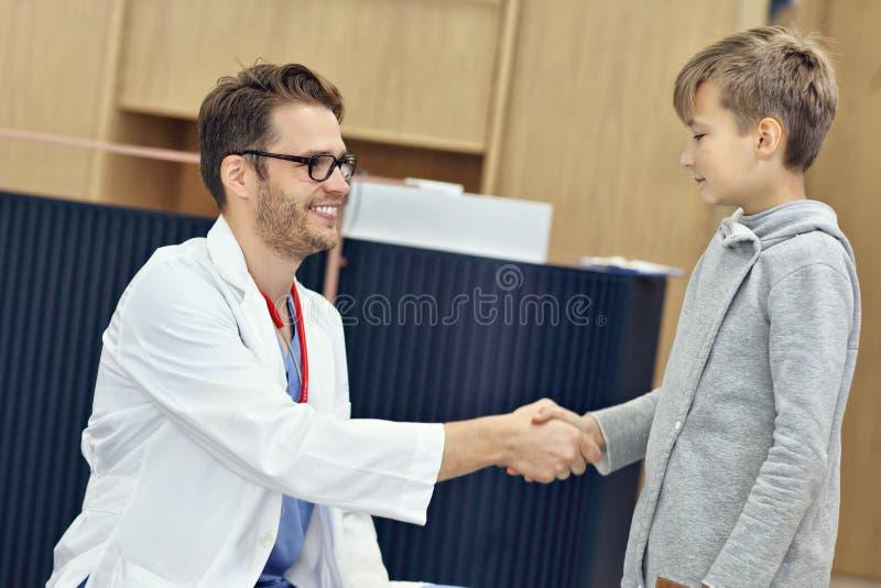 Doktorska powitalna młoda chłopiec w klinice zdjęcie royalty free