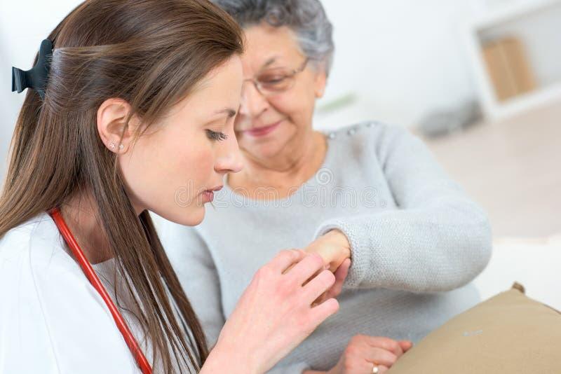 Doktorska sprawdza starsza damy ` s ręka zdjęcia royalty free