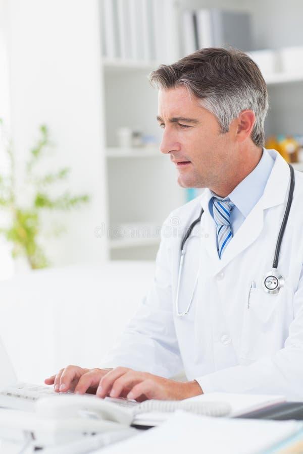 Doktorska używa komputerowa klawiatura przy stołem fotografia royalty free