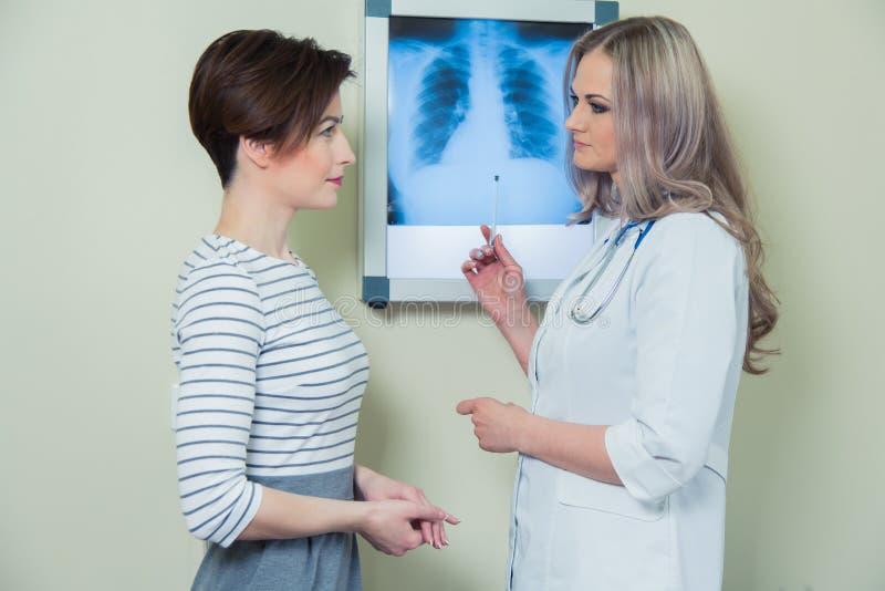 Doktorska wyjaśnia diagnoza jej żeński pacjent analizuje promieniowanie rentgenowskie fotografię zdjęcia royalty free