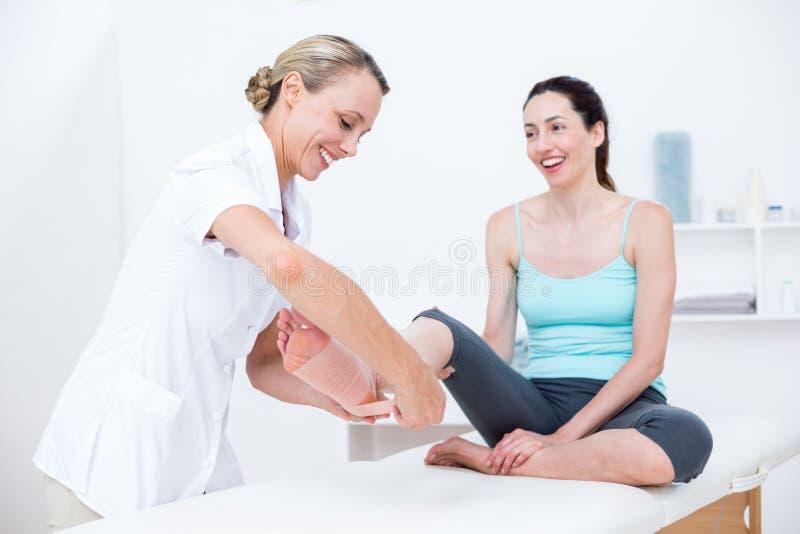 Doktorski bandażujący jej cierpliwą kostkę obraz royalty free