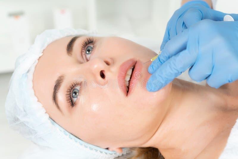 Doktorski cosmetologist robi Odmłodnieje twarzowej zastrzyk procedurze dla augmentationon warg kobiety w piękno salonie fotografia stock