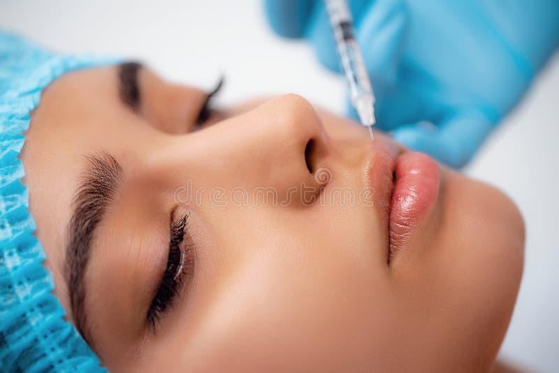 Doktorski cosmetologist robi Odmłodnieje twarzowej zastrzyk procedurze dla dociskać i gładzący marszczy na zdjęcia royalty free