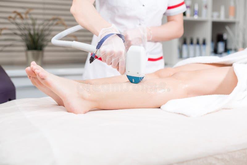 Doktorski cosmetologist robi procedurze młodej dziewczyny blondynki Laserowa epilacja i kosmetologia Włosiany usunięcie na damach obraz royalty free