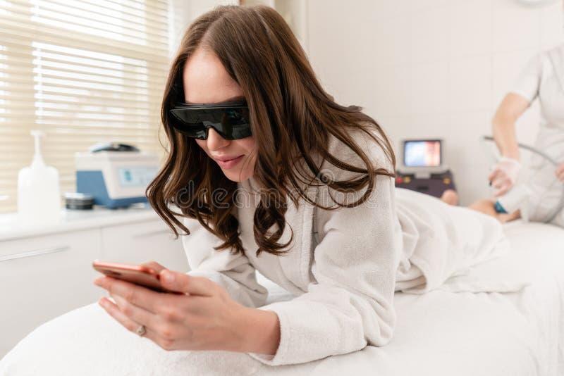 Doktorski cosmetologist robi procedurze m?odej dziewczyny brunetce Laserowa epilacja i kosmetologia W?osiany usuni?cie na damach obrazy stock