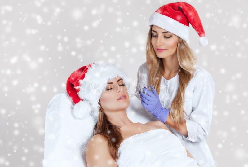Doktorski cosmetologist robi zastrzykowi na twarzy skórze wargach piękny i, młoda kobieta w Święty Mikołaj kapeluszu zdjęcia stock