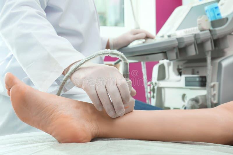 Doktorski dyrygentura ultradźwięku egzamin pacjent noga w klinice obrazy stock