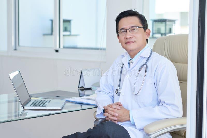 Doktorski działanie przy jego biurem zdjęcie stock