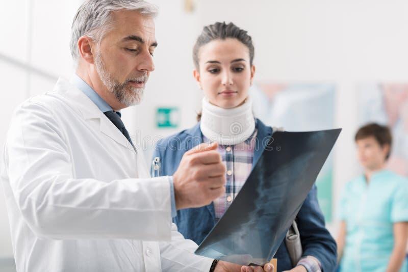 Doktorski egzamininujący pacjenta młodego żeńskiego promieniowanie rentgenowskie fotografia stock