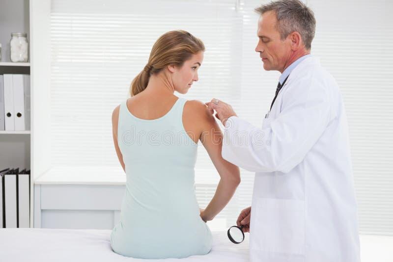 Doktorski egzamininujący pacjenta ramię fotografia royalty free
