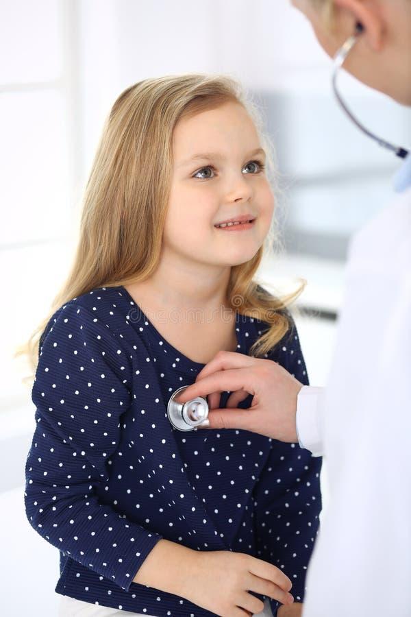 Doktorski egzamininuj?cy dziecko pacjenta stetoskopem ?liczna dziewczynka przy lekarza spotkaniem poj?cie k?ama medycyny pieni?dz obraz stock