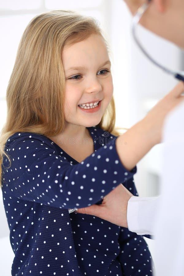 Doktorski egzamininuj?cy dziecko pacjenta stetoskopem ?liczna dziewczynka przy lekarza spotkaniem poj?cie k?ama medycyny pieni?dz zdjęcie royalty free