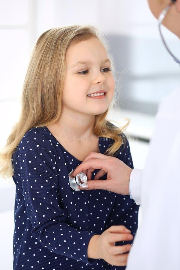 Doktorski egzamininuj?cy dziecko pacjenta stetoskopem ?liczna dziewczynka przy lekarza spotkaniem poj?cie k?ama medycyny pieni?dz zdjęcia stock
