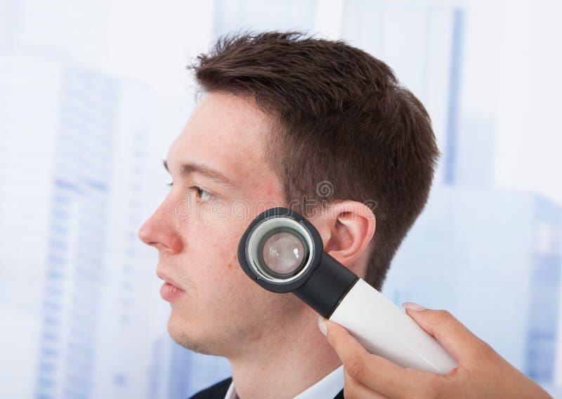 Doktorski egzamininuje biznesmen z dermoscope zdjęcie royalty free