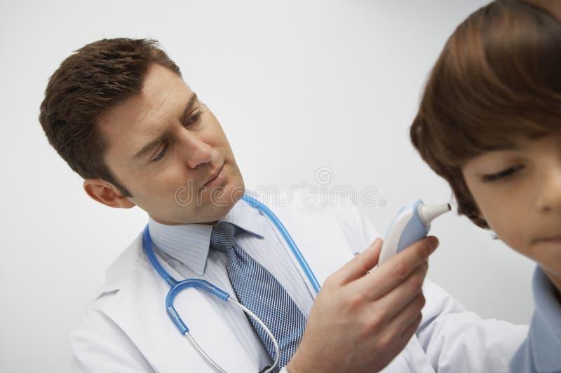 Doktorski Egzamininuje chłopiec ucho fotografia stock