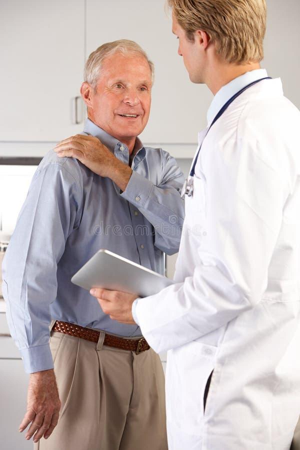 Doktorski Egzamininuje Męski pacjent Z ramię bólem zdjęcia stock