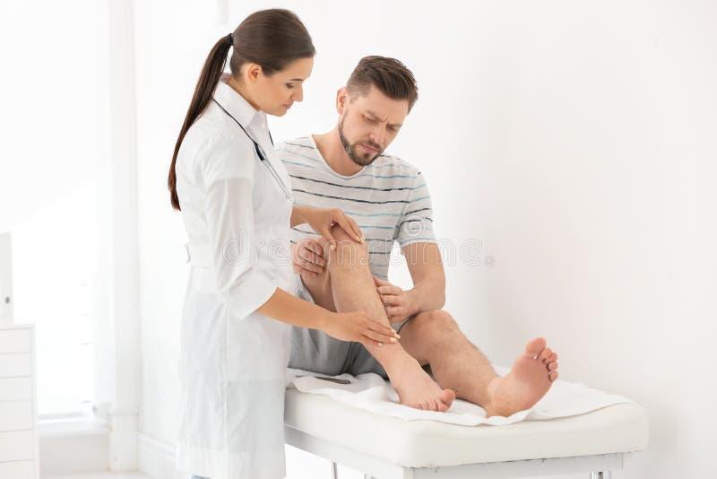 Doktorski egzamininuje męski pacjent z zdradzoną nogą obraz royalty free