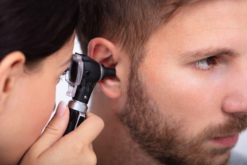Doktorski Egzamininuje pacjenta M?ski ucho fotografia stock