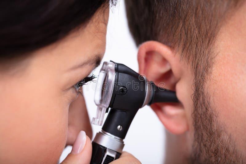Doktorski Egzamininuje pacjenta M?ski ucho obrazy royalty free
