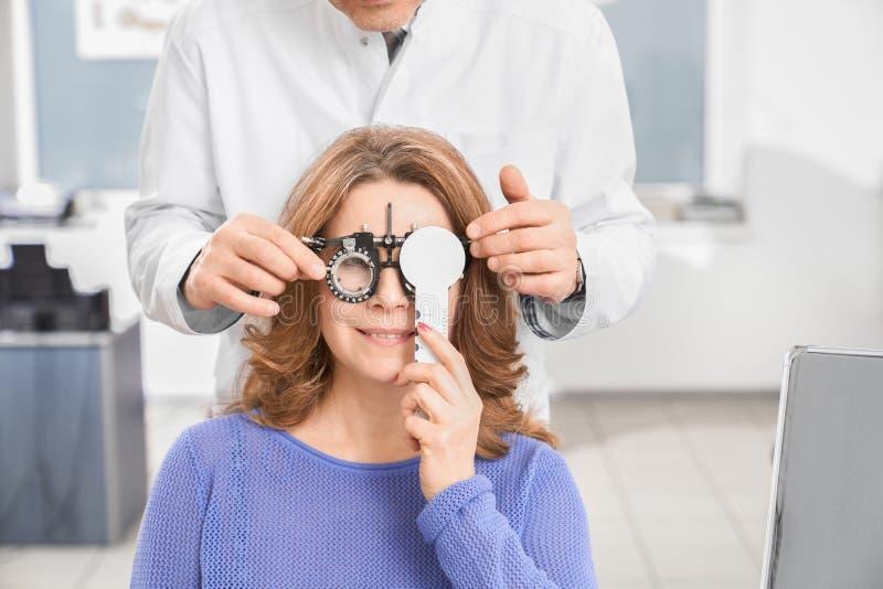 Doktorski egzamininuje wzroku pacjent z próbnymi szkłami fotografia stock